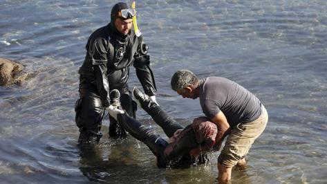 Tragedia. Un buzo saca del agua a una de las personas ahogadas en el naufragio. /REUTERS